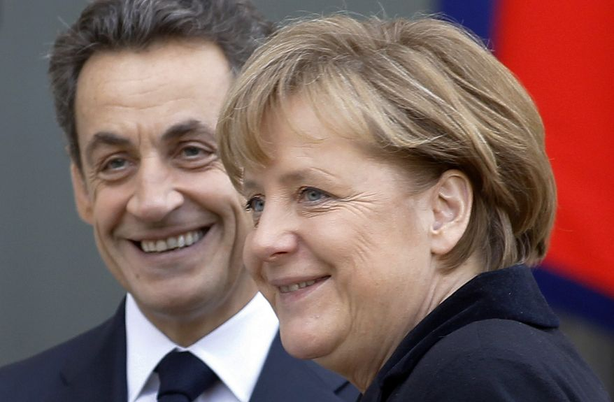 French President Nicolas Sarkozy (left) smiles as he greets German Chancellor Angela Merkel prior to their meeting at the Elysee Palace in Paris on Monday, Dec. 5, 2011. (AP Photo/Remy de la Mauviniere)
