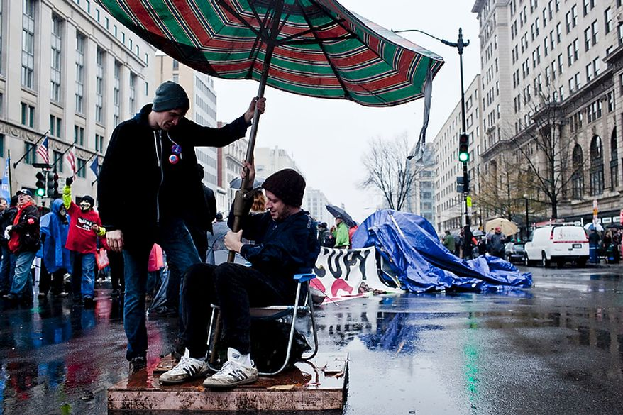 Kelly Mears, of Tacoma Park, Md., seated, gets a hand from another protestor in setting up an umbrella over his chair in the intersection of 15th St. NW and K St. NW as Occupy DC protestors block K St. NW in downtown Washington, D.C. on Dec. 7, 2011. (T.J. Kirkpatrick/ The Washington Times)