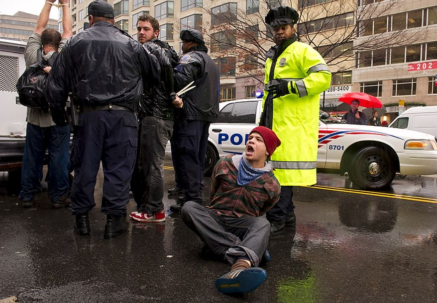 A man is arrested along K Street NW by Washington D.C. Metro police during a protest at the intersection of 14th and K Streets NW in Washington, D.C., Wednesday, December 7, 2011. Police also used horses to try to keep order in this situation. (Rod Lamkey Jr./The Washington Times)