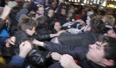 Opposition activists (left) and members of pro-Kremlin youth movements scuffle during demonstrations in Triumphal Square in Moscow on Tuesday, Dec. 6, 2011. (AP Photo/Ivan Sekretarev)