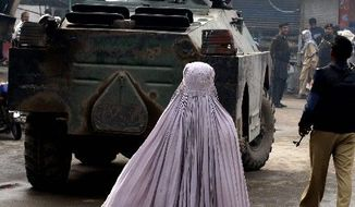 A Pakistani woman walks near a bazaar in Peshawar that was attacked by suspected militants. The death toll from suicide attacks in Pakistan in the first 11 months of 2011 has dropped almost 40 percent from last year. (Associated Press)
