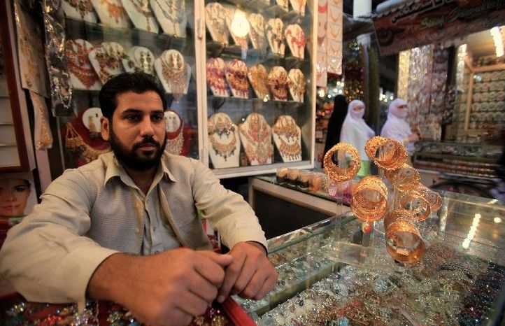 Pakistani shopkeeper Mohammad Hasib sits in his newly built shop that was destroyed two years ago in a car bombing that claimed the life of his older brother and more than 100 other people. Business is improving, thanks to a significant drop in militant violence in Pakistan this year. (Associated Press)
