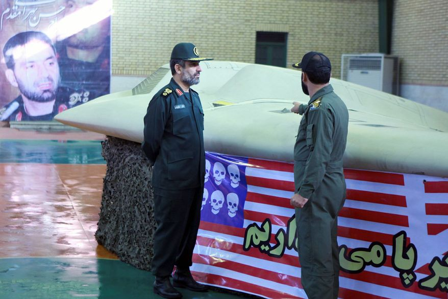 ** FILE ** This photo released on Thursday, Dec. 8, 2011, by the Iranian Revolutionary Guard claims to show the chief of the aerospace division of the Guard, Gen. Amir Ali Hajizadeh (left), listening to an unidentified colonel as he points to a U.S. RQ-170 Sentinel drone that Tehran said its forces had downed earlier in the week. (AP Photo/Sepahnews)