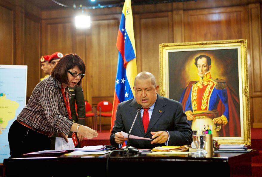 Venezuela's President Hugo Chavez, right, reviews papers with an assistant before a press conference with foreign media members at Miraflores presidential palace in Caracas, Venezuela, Tuesday, Dec. 6, 2011. The painting at back depicts Venezuela's Independence hero Simon Bolivar. (AP Photo/Ariana Cubillos)