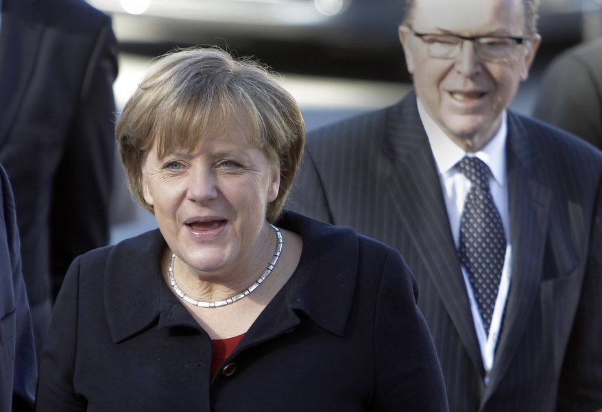 German Chancellor Angela Merkel arrives with European People's Party President Wilfried Martens for the 20th Congress of the EPP in Marseille, France, on Thursday, Dec. 8, 2011. (AP Photo/Lionel Cironneau)