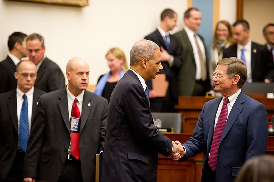 """U.S. Attorney General Eric Holder greets Congressman Lamar Smith (R-Tex.), right, as he appears before the House Judiciary Committee to answer questions about """"Fast and Furious"""" a federal gun sting which allowed weapons to go to Mexican drug cartels through straw buyers, Thursday, December 8, 2011. (Andrew Harnik / The Washington Times)"""