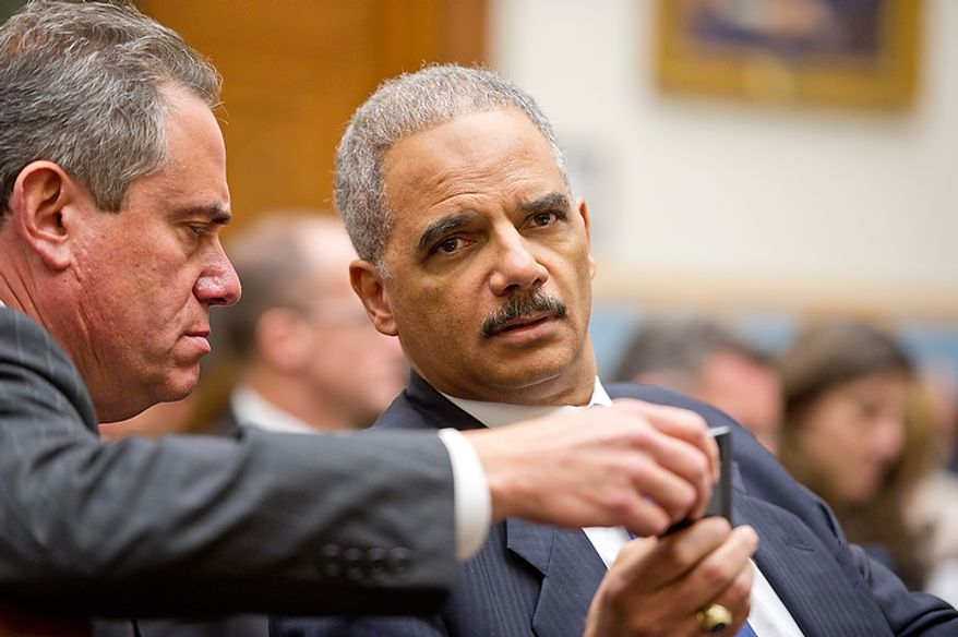 """U.S. Attorney General Eric Holder talks with a staff member before giving testimony in front of the House Judiciary Committee to answer questions about """"Fast and Furious"""" a federal gun sting which allowed weapons to go to Mexican drug cartels through straw buyers, Thursday, December 8, 2011. (Andrew Harnik / The Washington Times)"""