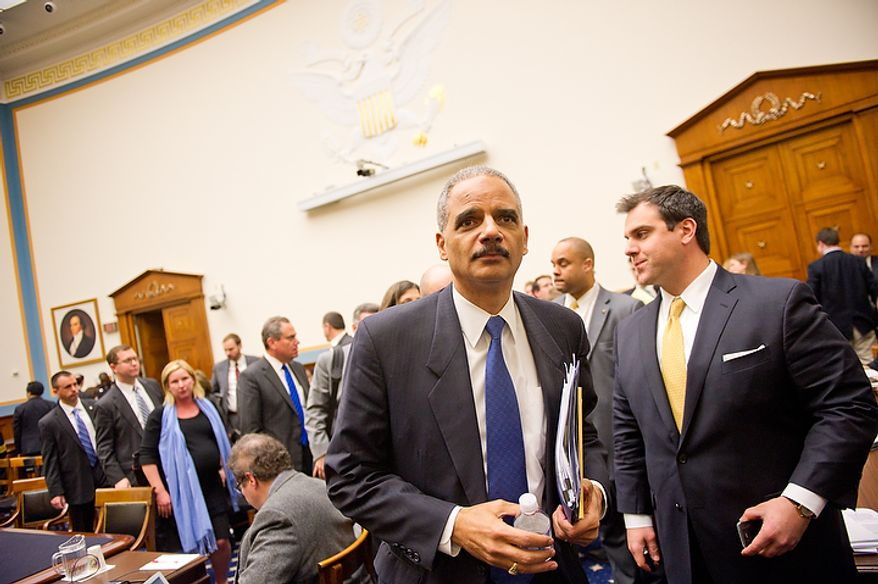 """U.S. Attorney General Eric Holder departs after appearing before the House Judiciary Committee to answer questions about """"Fast and Furious"""" a federal gun sting which allowed weapons to go to Mexican drug cartels through straw buyers, Thursday, December 8, 2011. (Andrew Harnik / The Washington Times)"""
