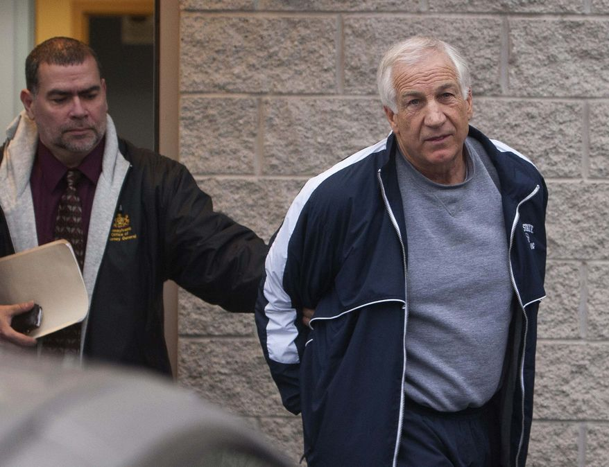 Former Penn State assistant football coach Jerry Sandusky, right, leaves the office of Centre County District Justice Daniel A. Hoffman under escort by Pennsylvania State Police and Attorney General's Office officials in Bellefonte, Pa., on Thursday, Dec. 7, 2011. (AP Photo/The Patriot-News, Andy Colwell)