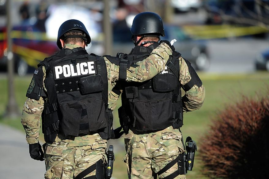 Virginia Tech police officers console one another as they move toward the scene where a fellow police officer was killed in a parking lot on the campus of Virginia Tech, Thursday  December 8, 2011, in Blacksburg, Va.  A man killed a police officer and another person after a traffic stop Thursday at Virginia Tech, sending a shudder through campus as students and faculty were told to stay inside and police searched for the gunman, school officials said. (AP Photo/Don Petersen)