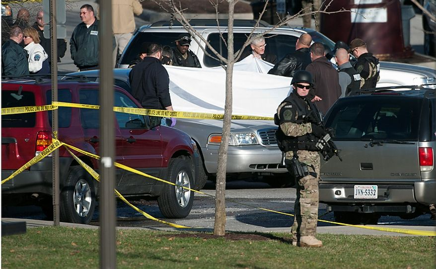 Police officials examine the body of a police officer shot to death in a parking lot on the campus of Virginia Tech,  Thursday, Dec. 8, 2011, in Blacksburg, Va.   The school said a police officer pulled someone over for a traffic stop and was shot and killed. The shooter ran toward a nearby parking lot, where a second person was found dead.   It was the first gunfire on campus since 33 people were killed in 2007 in the deadliest mass shooting in modern U.S. history. The deaths came on the same day university officials were in Washington appealing a fine that federal officials gave them over the school's response five years ago. (AP Photo/Don Petersen)