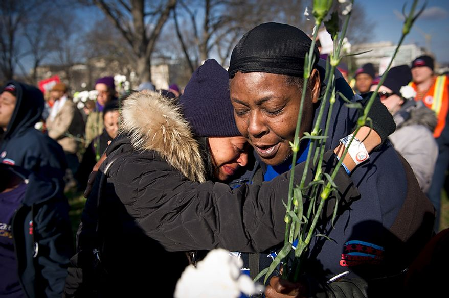 """Hilary Addison (left) cries on the shoulder of Minnie Lee both of Chicago, Ill., during the singing of the song """"We Shall Overcome"""" as they join people from organizations from across the United States such as the Service Employees International Union (SEIU) at Upper Senate Park in Washington, D.C., Thursday, December 8, 2011, for an Interfaith Service for the Jobless, with unemployed workers and faith leaders. They are calling on Congress not to cut jobs and for the extension of unemployment insurance, which is set to expire at the end of the year unless Congress takes action. """"I'm fighting for our people"""" said Ms. Lee. (Rod Lamkey Jr./The Washington Times)"""