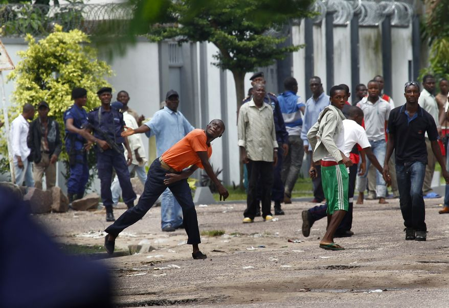 Supporters of Congolese opposition leader Etienne Tshisekedi hurl stones at Congolese riot police outside their candidate's headquarters in Kinshasa, Democratic Republic of Congo, Thursday, Dec. 8, 2011. (AP Photo/Jerome Delay)