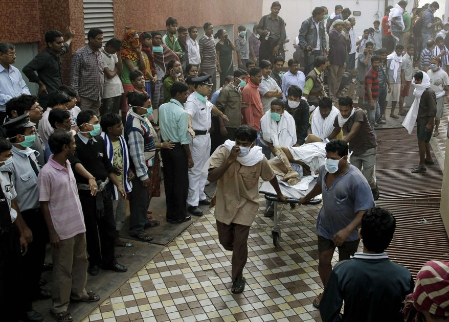 People help carry a patient out of a hospital after it caught fire in Kolkata, India, Friday, Dec. 9, 2011. The fire swept through the hospital early Friday, sending emergency workers scrambling to evacuate patients and medical staff from the smoke-filled building, officials said. (AP Photo/Bikas Das)