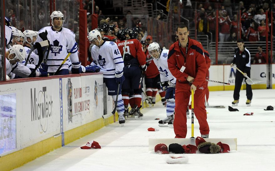 Toronto Maple Leafs players leave the ice as a crew member gathers up caps after Washington Capitals' Dennis Wideman earned a hat trick, scoring his third goal of the game, during the third period of an NHL hockey game, Friday, Dec. 9, 2011, in Washington. (AP Photo/Richard Lipski)