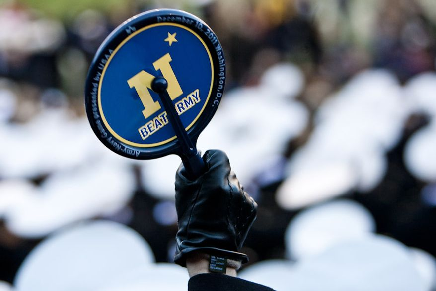 A Navy midshipmen cheers during the Army-Navy game, in Landover, Md. on Dec. 10, 2011. Navy beat Army 27-21 for it's 10th win in a row.(T.J. Kirkpatrick/ The Washington Times)