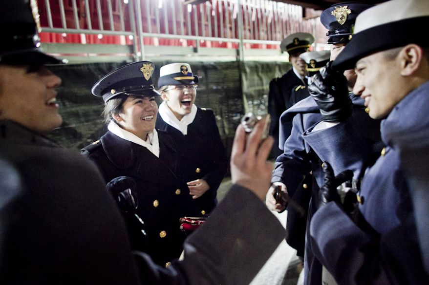 Midshipman Gabriela Baez, second from left, and Marci Demyon, center, react as Baez trades hats with Army 4th Class cadet Joe Giffin, right, after Navy beat Army 27-21, for it's 10th win in a row, at FedEx Field in Landover, Md. on Dec. 10, 2011. (T.J. Kirkpatrick/ The Washington Times)