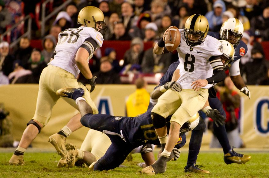 Navy Midshipmen linebacker Jarred Shannon (10) and Navy Midshipmen linebacker Matt Warrick (51) sack Army Black Knights quarterback Trent Steelman (8) late in the fourth quarter of the Army-Navy game at FedEx Field, Landover, MD, Saturday, Dec. 10, 2011. (Andrew Harnik / The Washington Times)