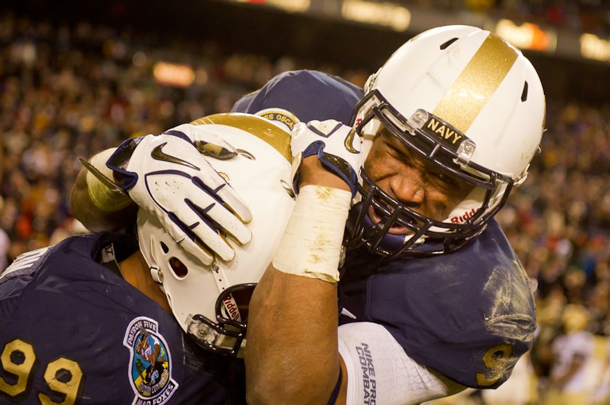 Navy Midshipmen defensive end Wes Henderson (99) and Navy Midshipmen safety Tra'ves Bush (9) celebrate as Navy wins 27-21 over Navy at FedEx Field, Landover, MD, Saturday, Dec. 10, 2011. (Andrew Harnik / The Washington Times)