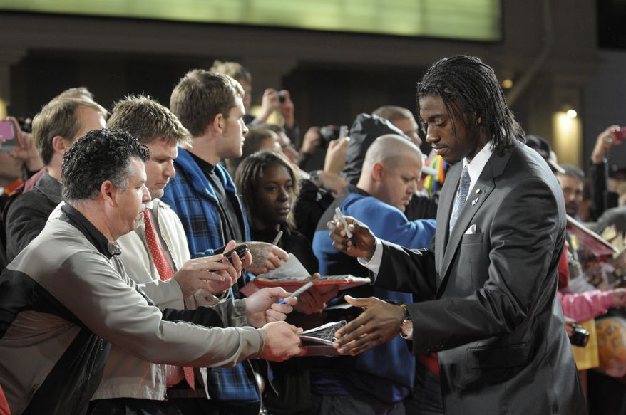 Baylor's Robert Griffin III, right, signs autographs on the red carpet for the College Football Awards ceremony in Lake Buena Vista, Fla., Thursday, Dec. 8, 2011.(AP Photo/Phelan M. Ebenhack)