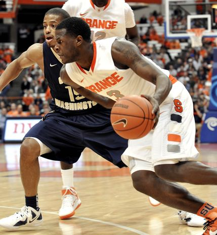 Syracuse's Dion Waiters, right, drives against George Washington's Aaron Ware during the second half of an in Syracuse, N.Y., Saturday, Dec. 10, 2011. Syracuse won 85-50. (AP Photo/Kevin Rivoli)