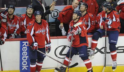 Washington Capitals defenseman Dennis Wideman and Brooks Laichsmile as they wait for the ice to be cleared after hats were thrown on the ice after what was originally ruled Wideman's hat trick, but later changed to Laich's goal against the Toronto Maple Leafs, Friday, Dec. 9, 2011, in Washington. won (AP Photo/Nick Wass)