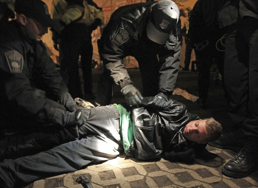 Boston police officers remove an Occupy Boston protester from Dewey Square in Boston before dawn Saturday, Dec. 10, 2011. More than 40 people were peacefully arrested as the park was cleared. The city had set a Thursday midnight deadline for protesters to leave or face eviction. (AP Photo/The Boston Globe, Essdras M Suarez, , Pool)