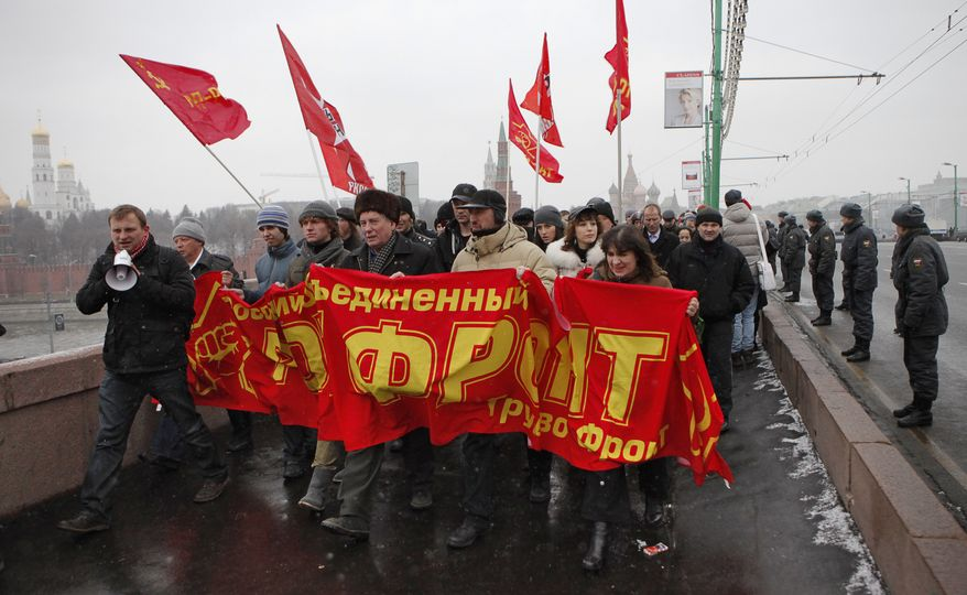 """Protesters hold a red banner that reads """"Rot Front"""" as they shout anti-Putin slogans during a mass rally in Moscow on Saturday, Dec. 10, 2011, to protest alleged vote rigging in Russia's recent parliamentary elections. (AP Photo/Alexander Zemlianichenko)"""