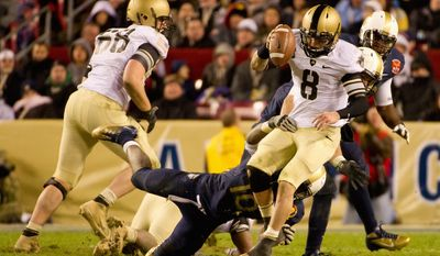 Navy linebackers Jarred Shannon (10) and Matt Warrick (obscured) sack Army quarterback Trent Steelman late in the fourth quarter during the annual matchup of the service academies. (Andrew Harnik/The Washington Times)