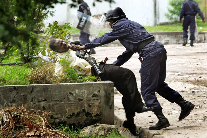 A Congolese riot-police officer restrains a supporter of Congolese opposition leader Etienne Tshisekedi outside the candidate's headquarters in Kinshasa, Congo, on Thursday. (Associated Press)