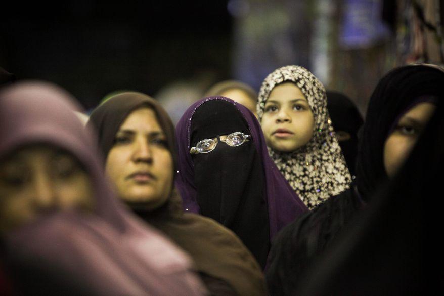 ** FILE ** Egyptian women listen during a Muslim Brotherhood campaign rally in Bashteil, a neighborhood of Cairo.(Associated Press)