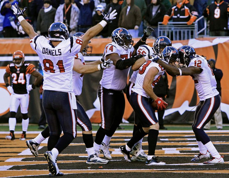 Texans wide receiver Kevin Walter (83) is mobbed by teammates after catching the winning touchdown Sunday at Cincinnati. (Associated Press)