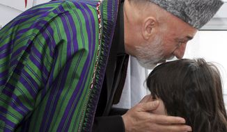 Afghan President Hamid Karzai talks with an girl who was wounded in Tuesday's suicide bomb attack against Shiites as he visits the victims at the Emergency Hospital in Kabul, Afghanistan, on Wednesday, Dec. 7, 2011. (AP Photo/S. Sabawoon, Pool)