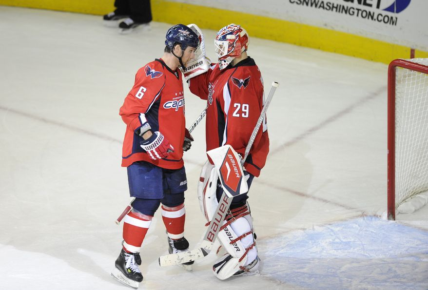 Washington Capitals defenseman Dennis Wideman celebrates the 4-2 win over the Toronto Maple Leafs with goalie Tomas Vokoun, Friday, Dec. 9, 2011, in Washington. (AP Photo/Nick Wass)