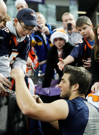 """Denver Broncos quarterback Tim Tebow signs some autographs before a game Dec. 4 in Minneapolis. Mr. Tebow's exploits, including an overtime win Sunday, have made him """"the talk of the NFL."""" (Associated Press)"""