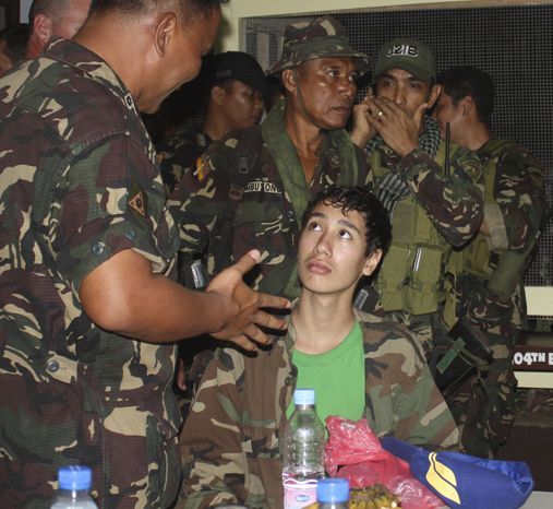 Kevin Lunsman, a kidnapped American teenage boy, talks Dec. 10, 2011, to Filipino soldiers inside the Philippine military compound in Zamboanga City, Philippines, following his escape from suspected al Qaeda-linked militants. (Associated Press)