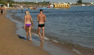 **FILE** A tourist couple walks Dec. 8, 2010, in the shallow waters at a closed beach in the Red Sea resort of Sharm el-Sheik, Egypt. (Associated Press)