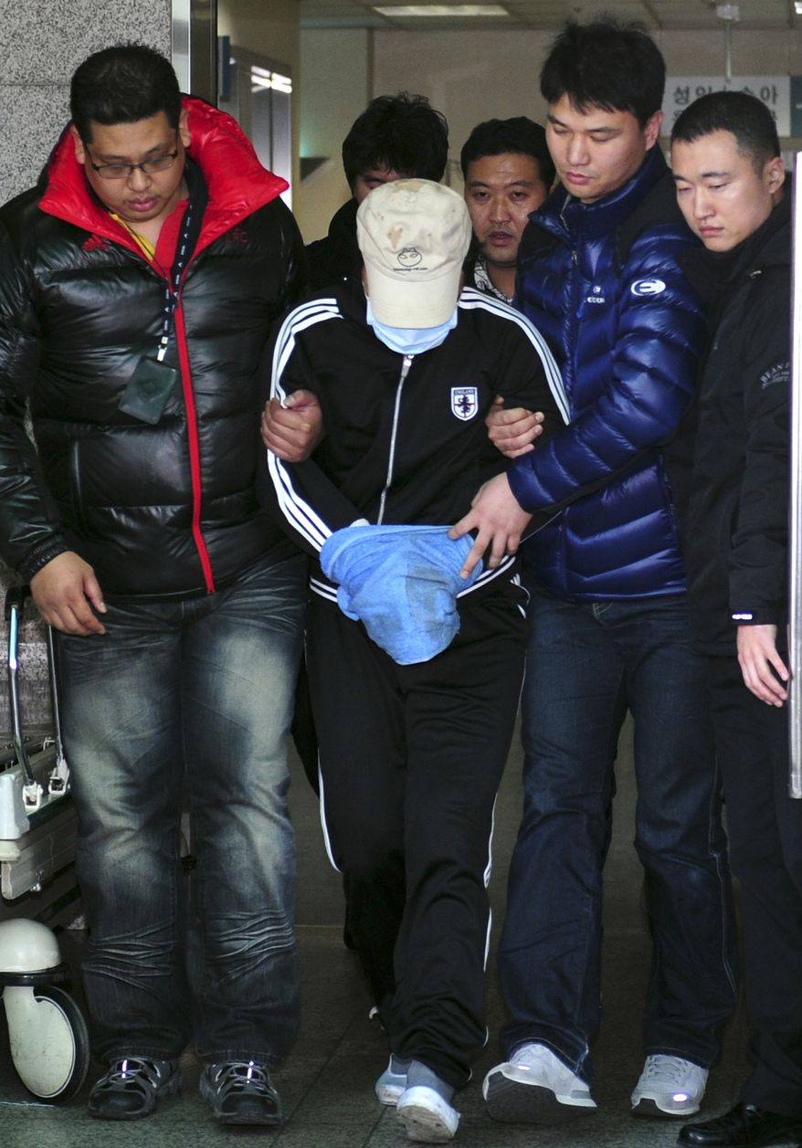 An unidentified Chinese fishing-boat captain (center) suspected of stabbing two South Korean coast guard officers is led by police officers to a coast guard office in Incheon, South Korea, after his arrest on Monday, Dec. 12, 2011. (AP Photo/Yonhap, Ha Sa-hun)