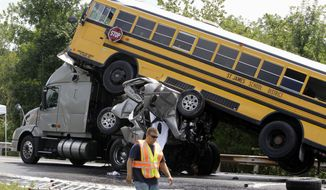 A rescue worker is seen Aug. 5, 2010, at the scene of an accident involving two school buses, a tractor-trailer and another passenger vehicle near Gray Summit, Mo. Federal safety investigators say a 19-year-old driver was texting at the time his pickup truck, two school buses and other vehicles collided in a deadly pileup on an interstate highway in Missouri. (Associated Press)