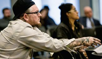 Matthew Knopp, owner of Tattoo Paradise, listens to testimony at the hearing. Several tattoo artists told committee members that reputable businesses already adhere to standards incorporated in the regulations being considered. (T.J. Kirkpatrick/The Washington Times)