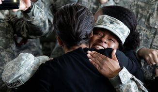 """First lady Michelle Obama welcomes a servicewoman in a maintenance hangar at Fort Bragg, N.C., on Wednesday. She told returnees that the president kept his promise """"to responsibly bring you home from Iraq."""" (Associated Press)"""