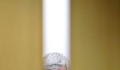 Former House Speaker Newt Gingrich, a GOP presidential hopeful, is seen through a window on a door as he spoke to students at the University of Iowa College of Public Health in Iowa City on Wednesday. Mr. Gingrich has been criticized for a $500,000 jewelry bill at Tiffany's. (Associated Press)