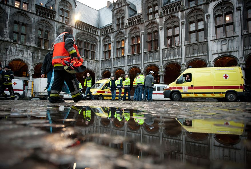 Police and rescuers work at a central square in Liege, Belgium, where a gunman lobbed grenades into and opened fire on a crowd of people on Tuesday, Dec. 13, 2011. (AP Photo/dapd, Timur Emek)