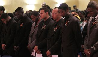 Florida A&M University drum majors pay their respects Nov. 22, 2011, during a memorial service in Tallahassee, Fla., for Robert Champion, a drum major for FAMU's Marching 100 band who was suspected of being hazed. (Associated Press/Tallahassee Democrat)