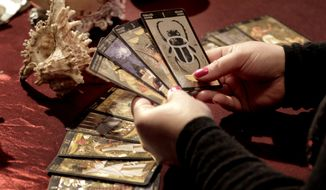 ** FILE ** Romanian witch Mihaela Minca holds cards during an interview with the Associated Press in January 2011 in Mogosoaia, Romania. (AP Photo/Vadim Ghirda, File)