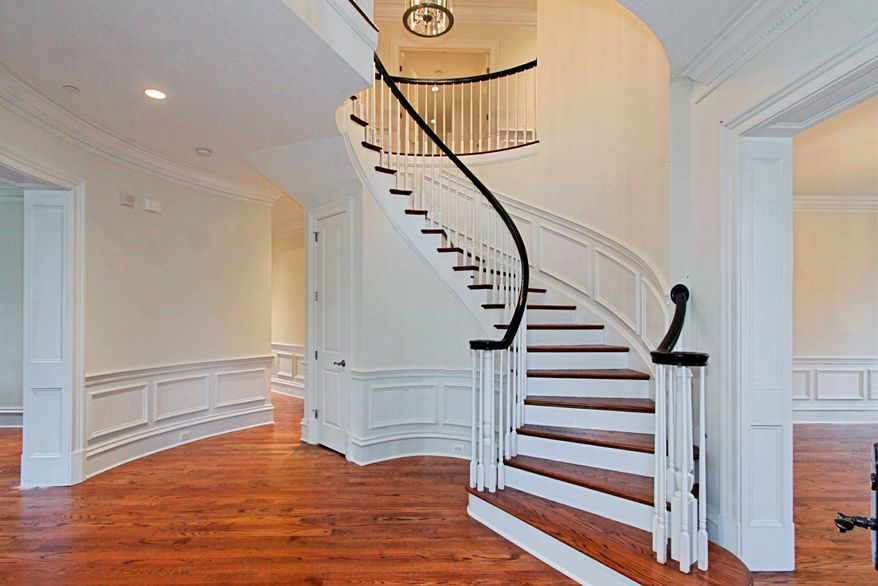 A dramatic curving staircase leads to the upper level.