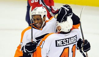 Philadelphia Flyers defenseman Andrej Meszaros congratulates teammate Wayne Simmonds for scoring in Tuesday night's 5-1 win over the Washington Capitals, as a glum Caps center Marcus Johansson looks on. (Associated Press)