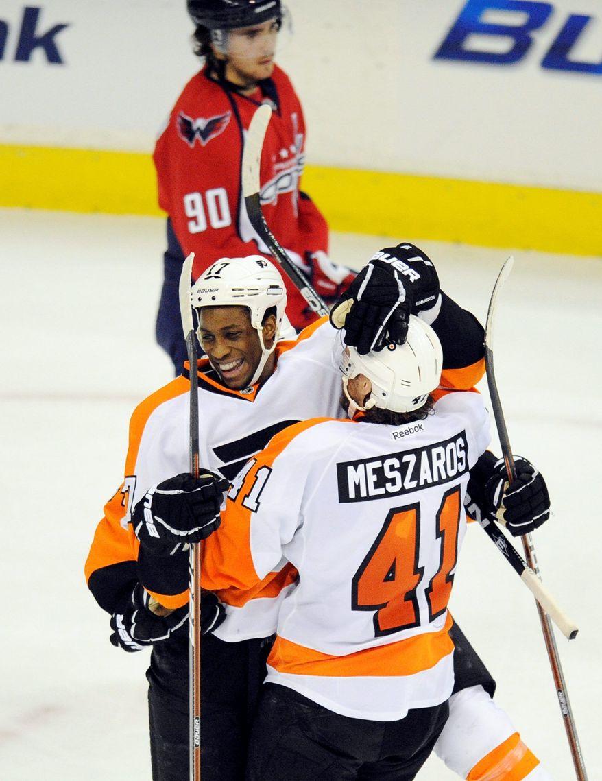 Philadelphia Flyers defenseman Andrej Meszaros congratulates teammate Wayne Simmonds for scoring in Tuesday night's 5-1 win over the Washington Capitals, as a glum Caps center Marcus Johansson looks on. (Associated Press)