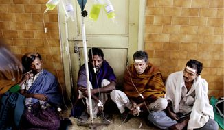Men hooked up to saline IVs crowd a hospital hallway in Diamond Harbor, India, on Thursday after drinking methanol-laced alcohol Tuesday night. The bootleg liquor has killed scores and sent scores more to hospitals. At least seven bootleggers have been arrested, and police were searching for two others suspected of supplying the spirits to poor villagers. (Associated Press)
