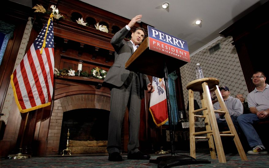 Texas Gov. Rick Perry speaks at Bayliss Park Hall in Council Bluffs, Iowa, during a campaign stop Wednesday. All of the GOP candidates were in Sioux City for the final scheduled debate of the year Thursday night. (Associated Press)